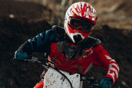 Person with helmet and goggles on riding a dirt bike.