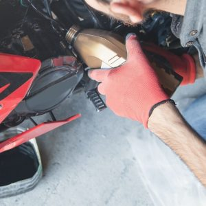 Person changing the oil in a motorcycle.