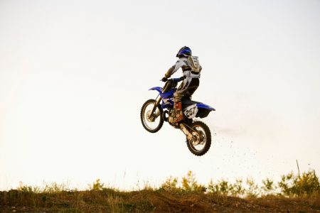 Person riding a dirt bike in an open field.