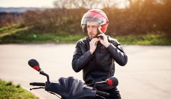 Man putting on helmet to ride a motorcycle.