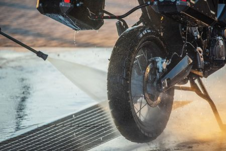 Person rinsing cleaner off motorcycle with a hose.