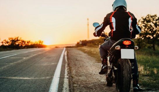 Man pulled to teh side of the road on a motorcycle